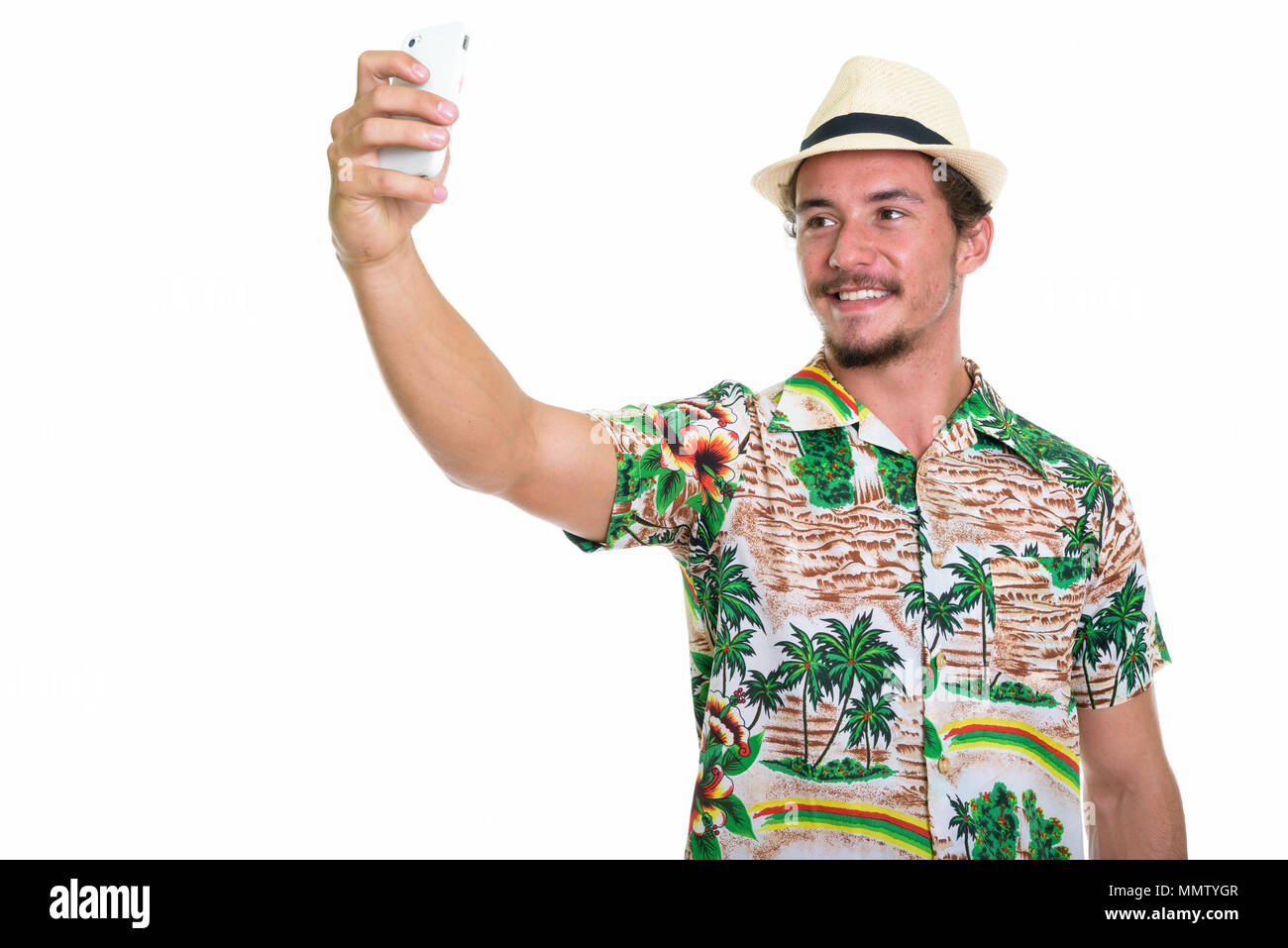 Studio shot of young happy tourist man smiling while taking self - Stock Image