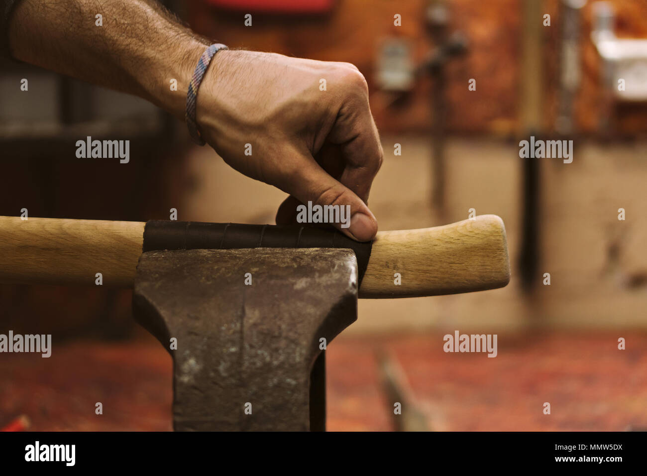 Man working in carpentry workshop. He checks leather winding on wooden handle of ax. Men at work. Hand work. - Stock Image