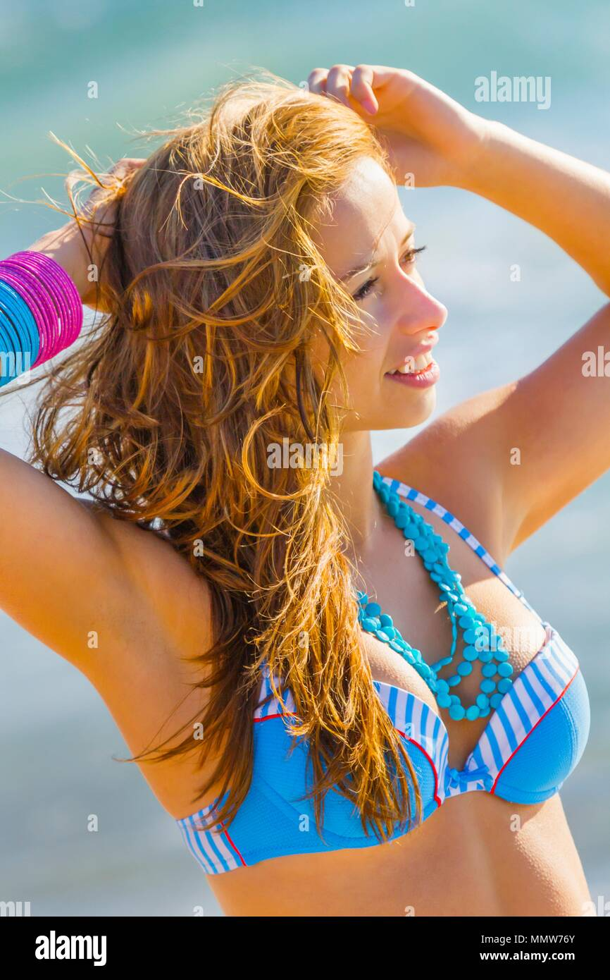Teen girl side view portrait headshot spontaneous fixing curly hair - Stock  Image