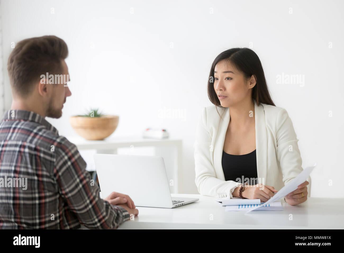 Distrustful serious asian businesswoman discussing business docu - Stock Image