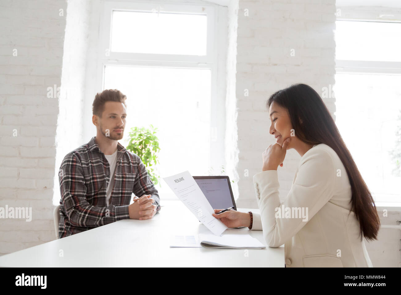 Smiling hr reading resume at job interview with serious candidat - Stock Image
