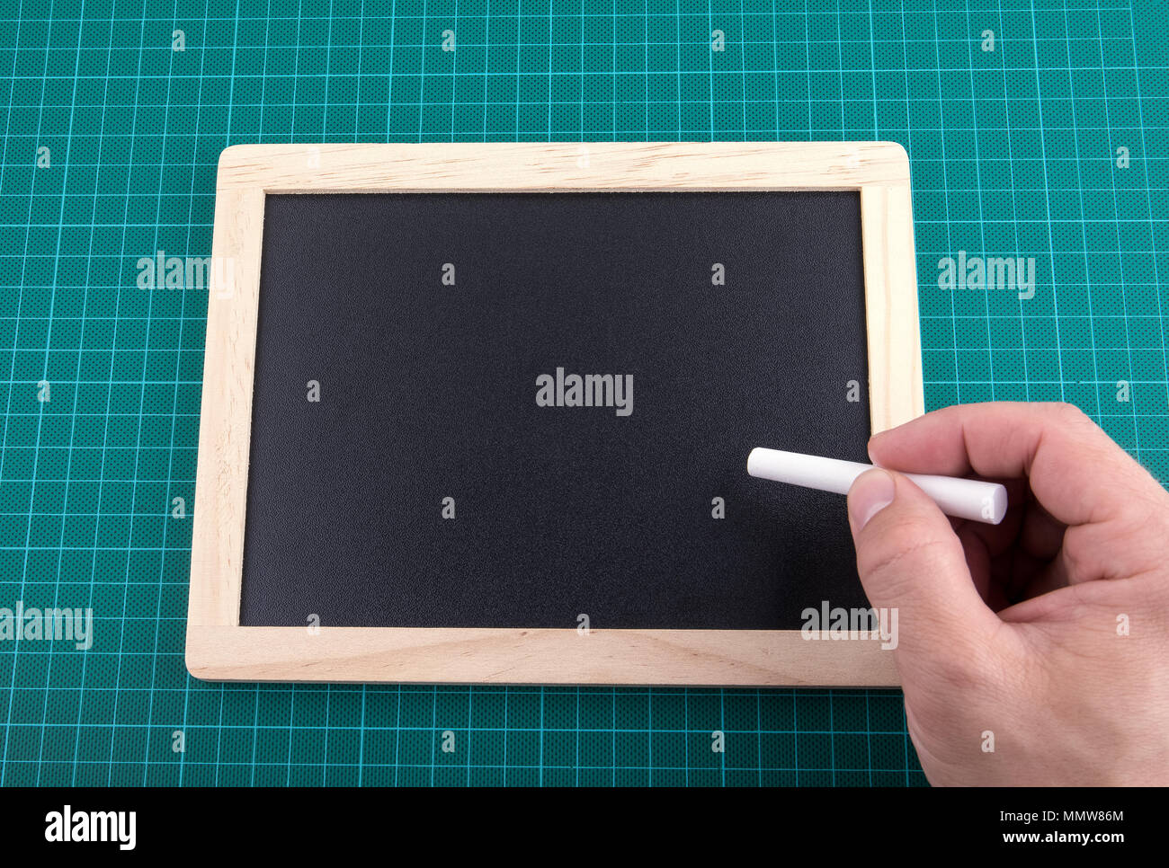 chalkboard and chalk on checked green backgrond, space for text - Stock Image