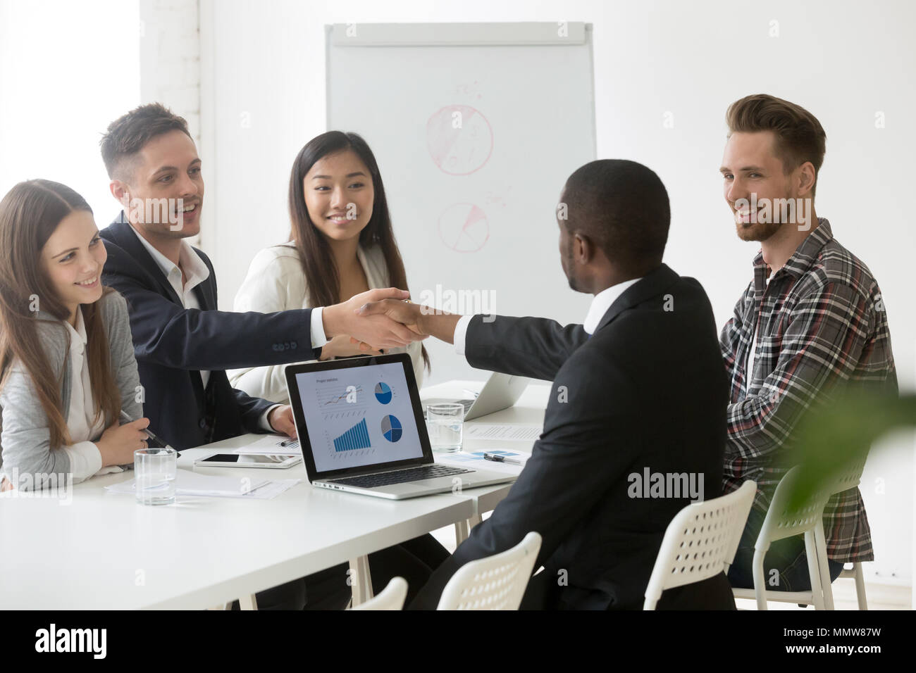 Satisfied multiracial businessmen handshaking after successful g - Stock Image
