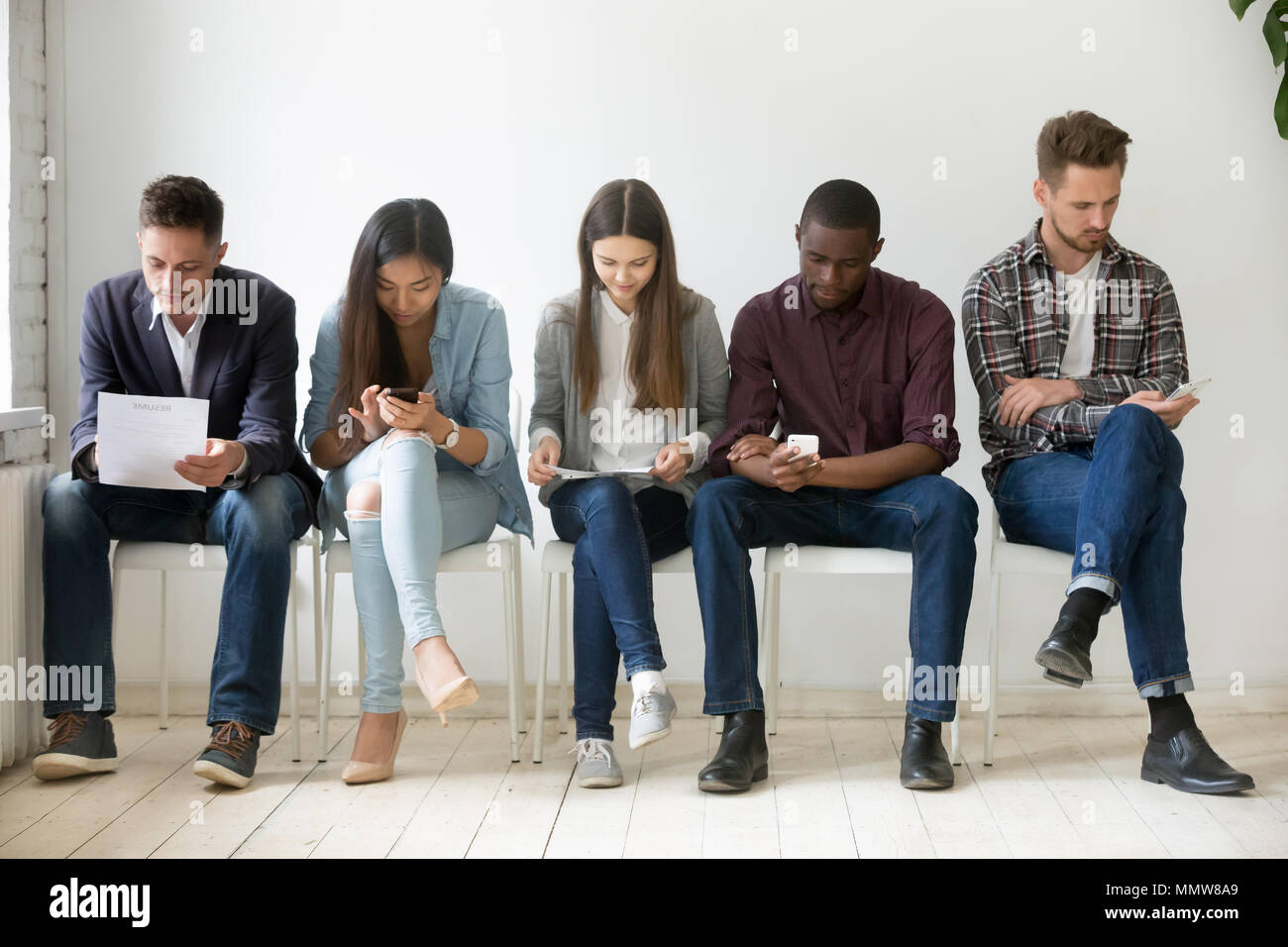 Multi-ethnic millennial people wait in queue preparing for job i - Stock Image