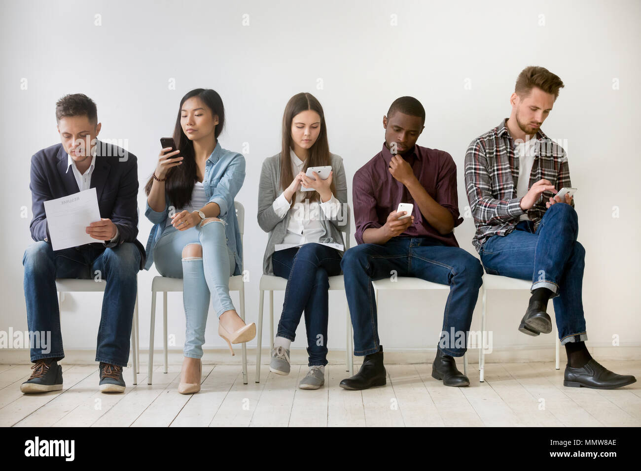 Diverse millennial people waiting in queue holding resumes using - Stock Image
