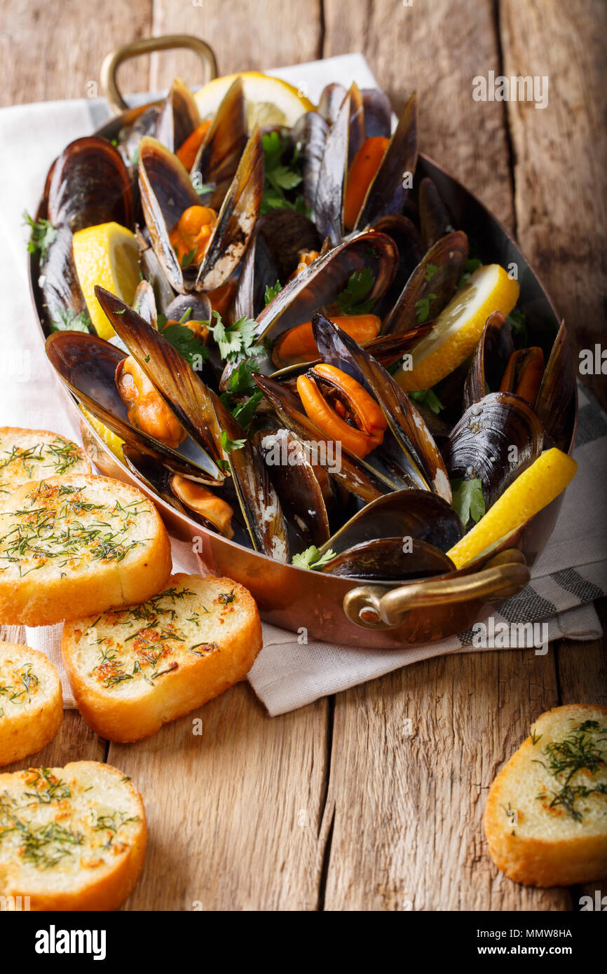 Copper pot of gourmet mussels with lemon, parsley and garlic served on a bread. vertical, rustic style - Stock Image