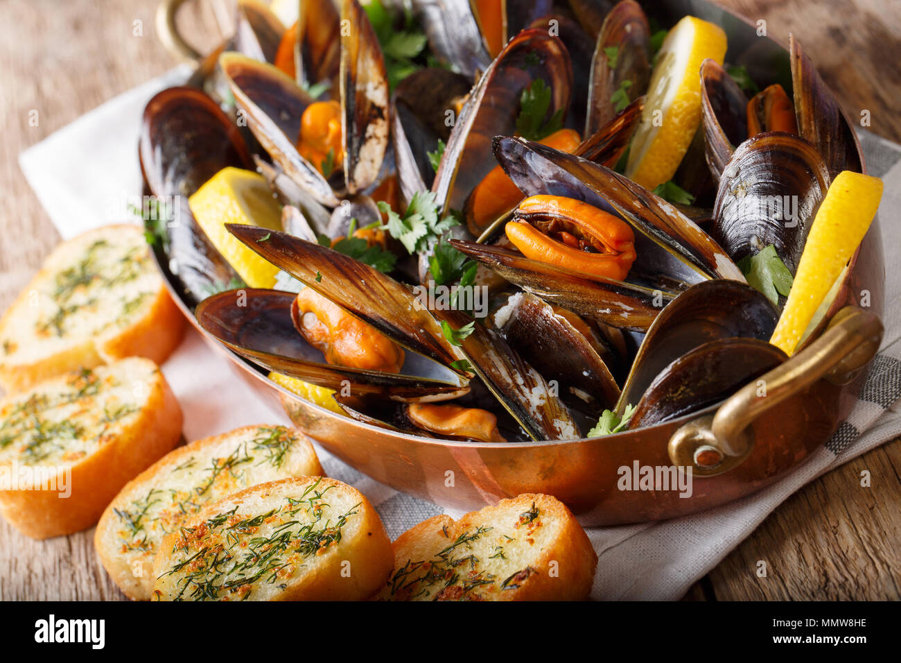Cooked mussels with lemon, parsley and garlic macro in a saucepan on a table. horizontal - Stock Image