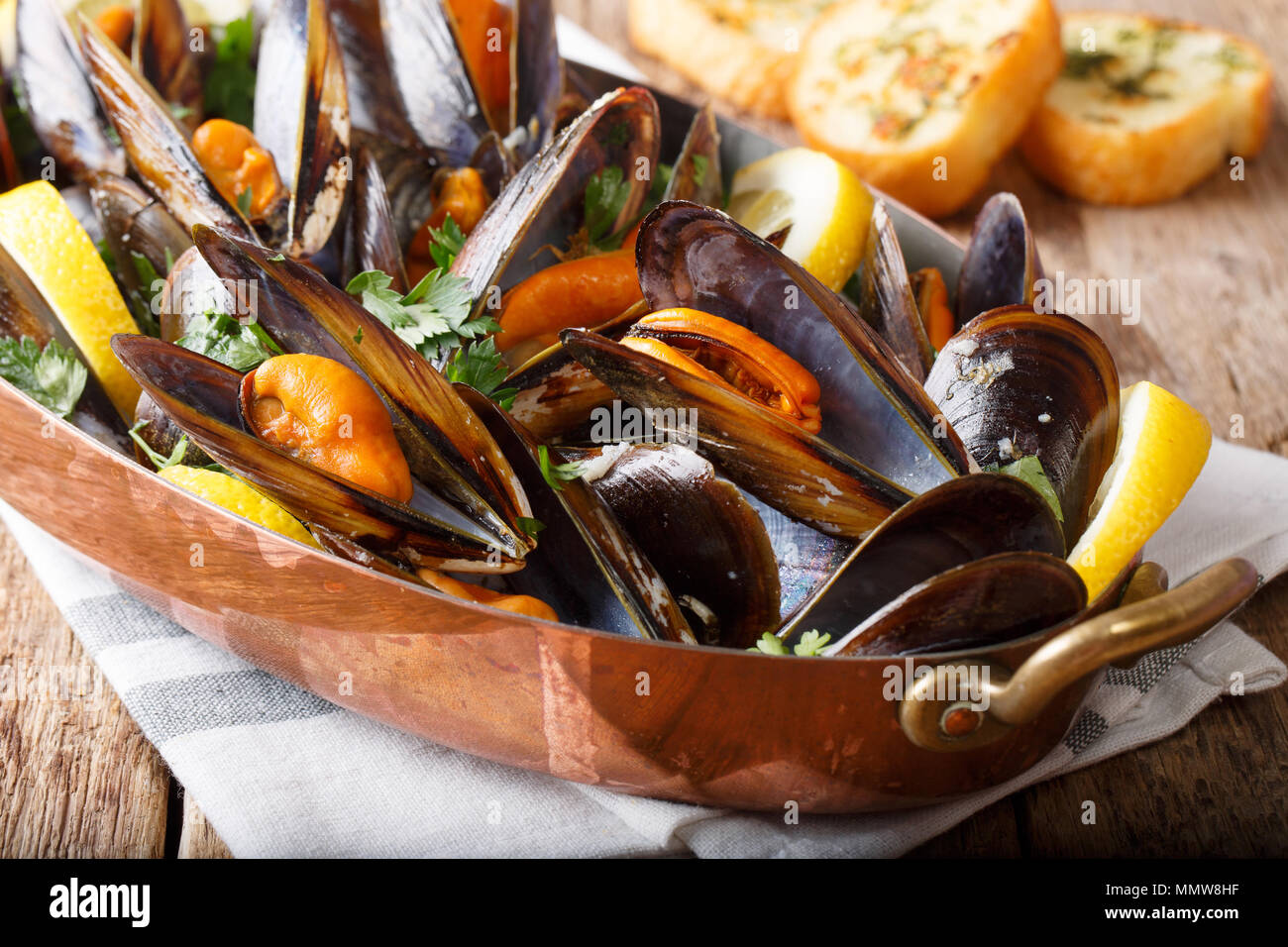 Mussels with lemon and garlic macro in a saucepan on a table. horizontal - Stock Image