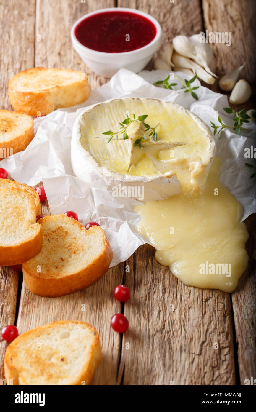 French melted Camembert with toast and cranberry sauce close-up on the table. vertical, rustic style - Stock Image