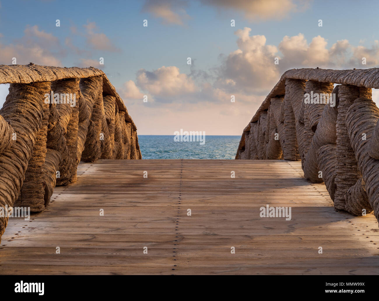 Wooden bridge made of palm trunks leading to the sea coast with partly cloudy sky in sunrise time at Montaza public park in summer time, Alexandria, E - Stock Image