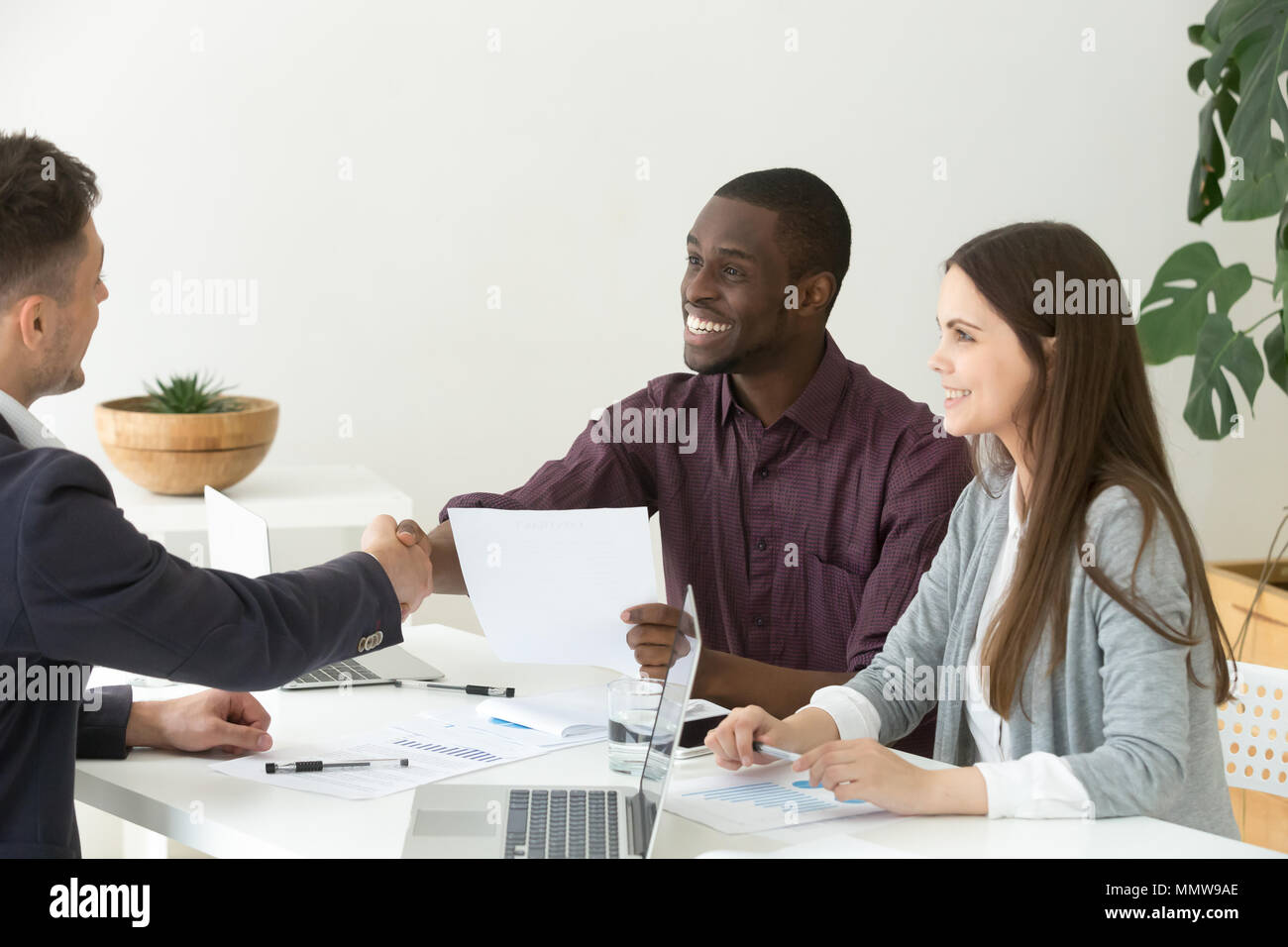 Ceo handshaking appreciating african project team leader for goo - Stock Image