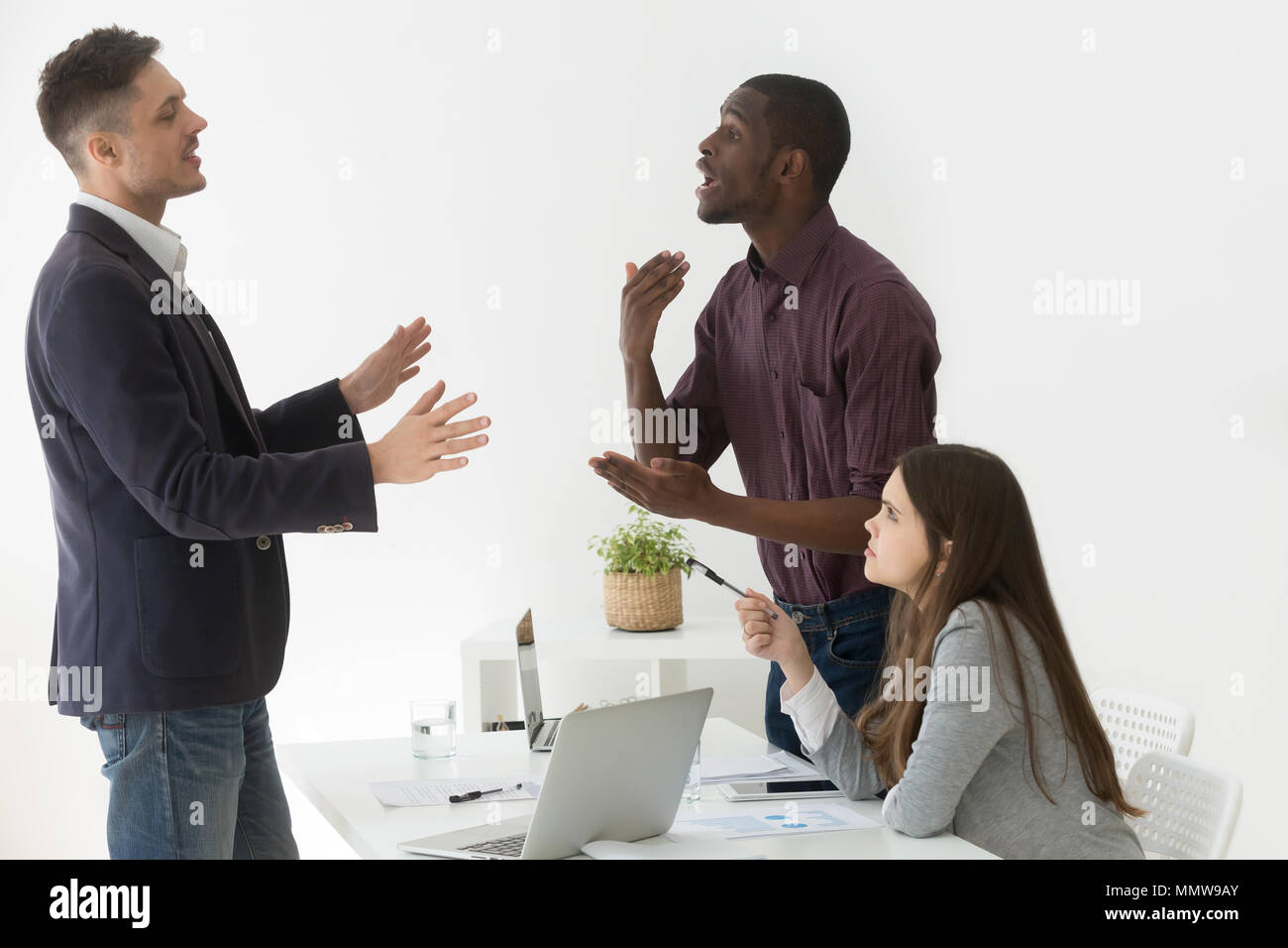 Diverse african and caucasian colleagues having dispute at group - Stock Image