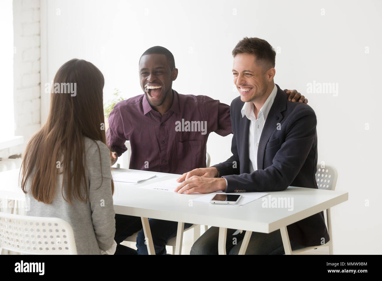 Multiracial hr managers laughing at funny joke interviewing woma - Stock Image