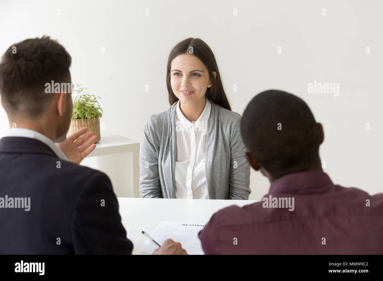 Confident applicant smiling at job interview with diverse hr man - Stock Image