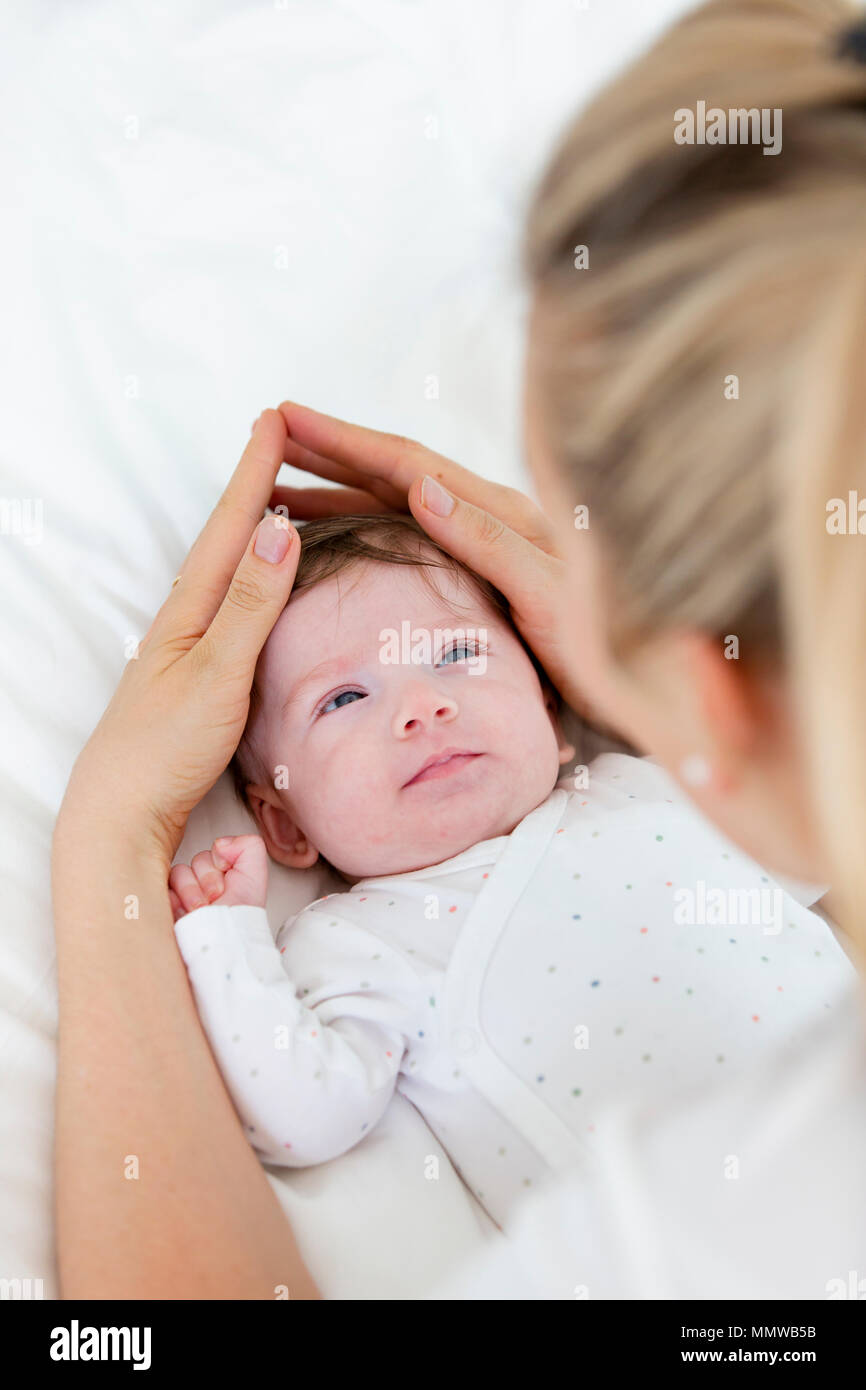 beautiful blond mother, woman massages her baby - Stock Image