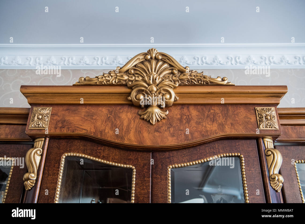 Luxury cupboard with stucco mouldings. Vintage woodworking and finishing on antique furniture. - Stock Image
