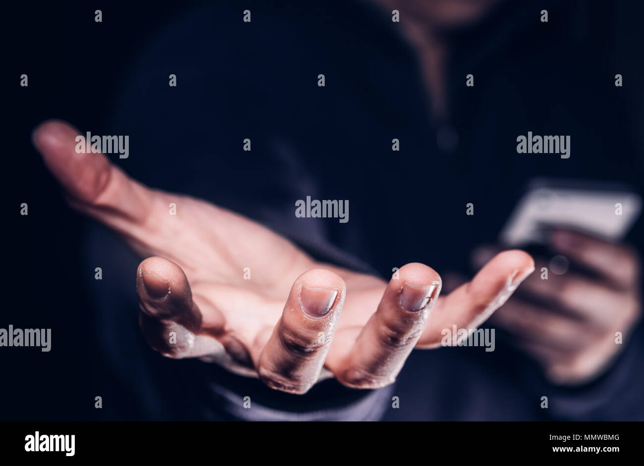 Hooded cyber crime hacker using mobile phone internet hacking in to cyberspace,online personal data security concept. - Stock Image