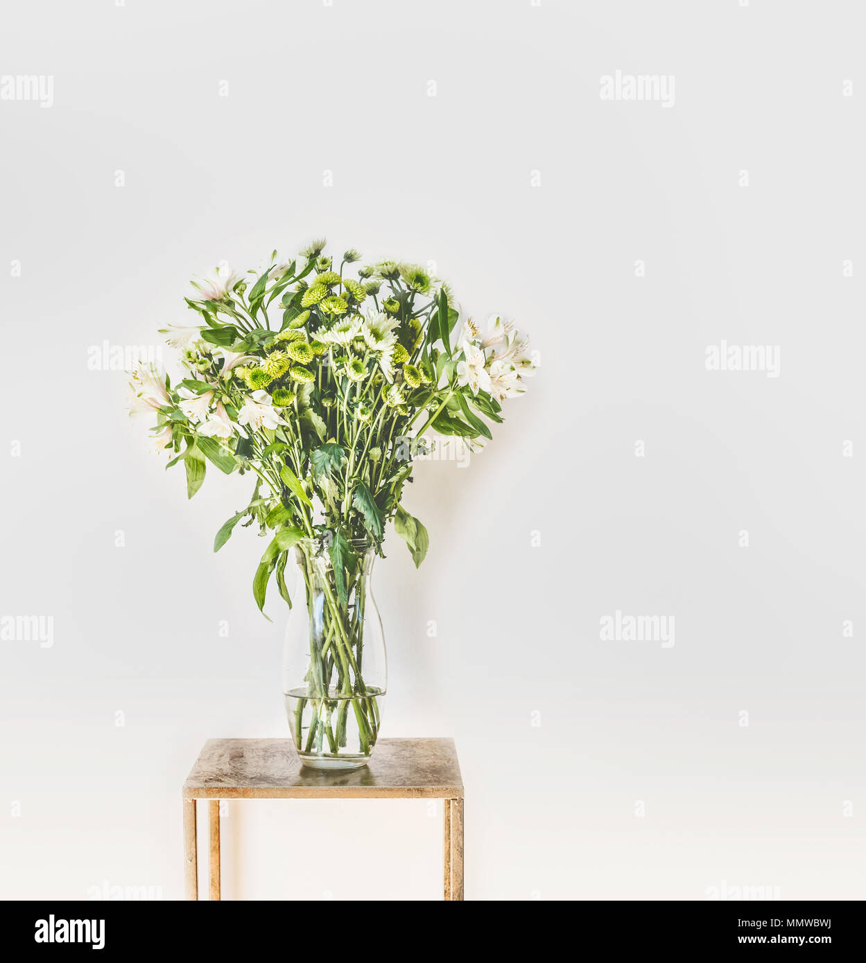 Beautiful green flowers bunch with falling petals in glass vase at white wall background. Home interior and decor ideas - Stock Image
