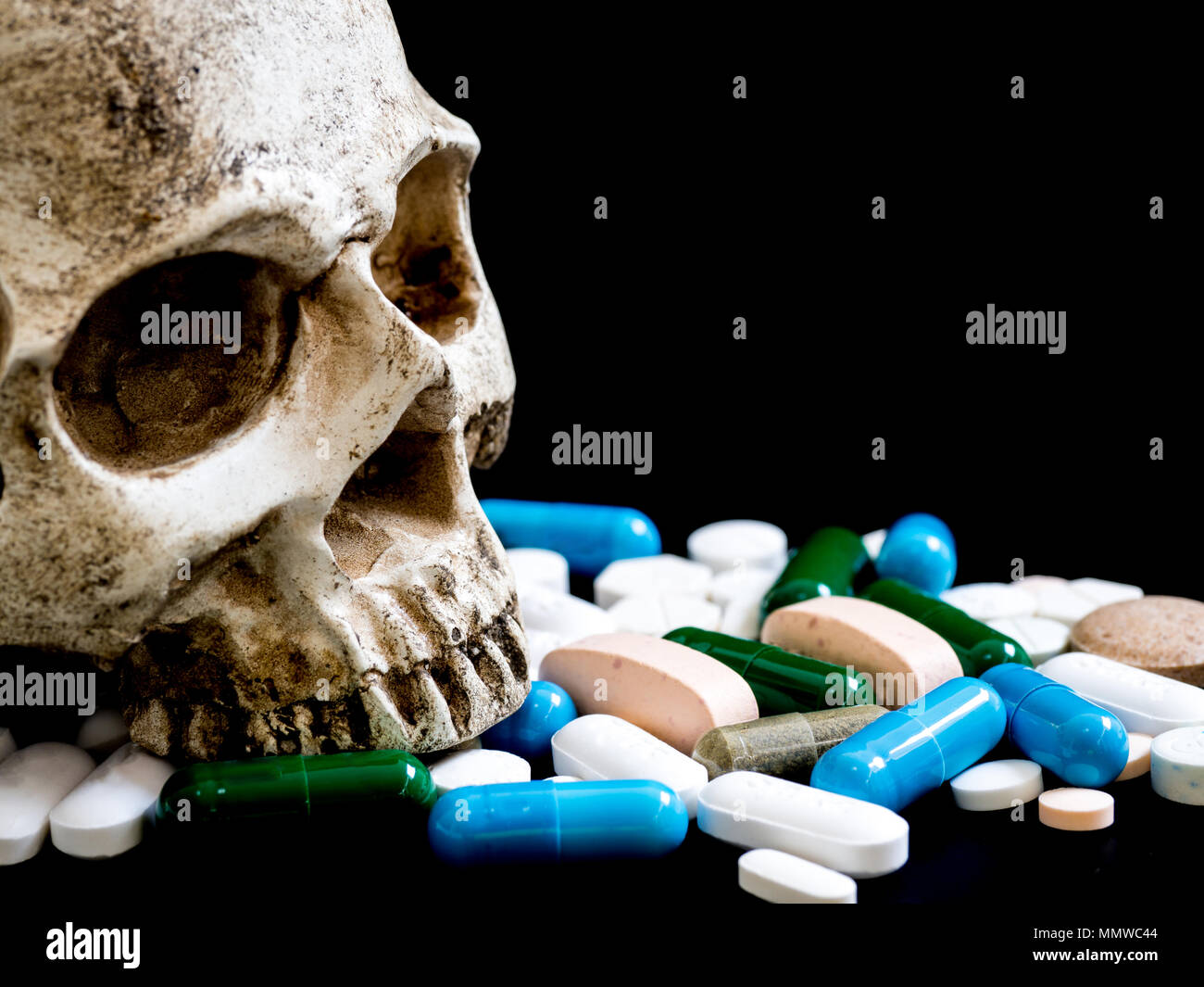 Human skull on multicolored of drug and capsule is on the black background. Close up. We are against drugs (anti drugs), cure in container for health. - Stock Image