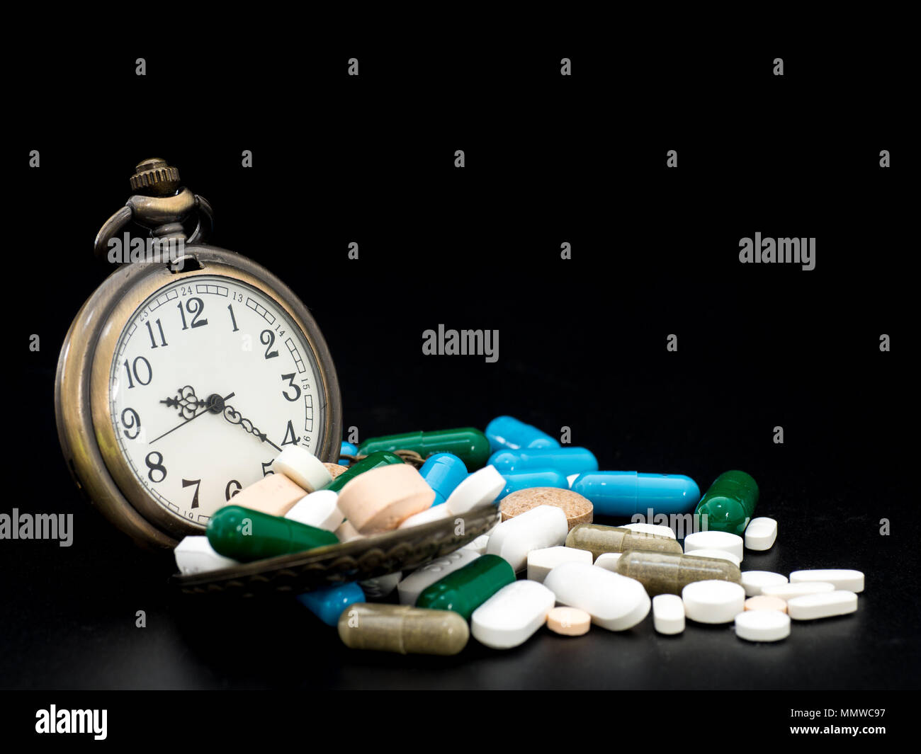 Antique clock on multicolored of drug and capsule is on the black background. Close up. We are against drugs (anti drugs), cure in container for healt - Stock Image