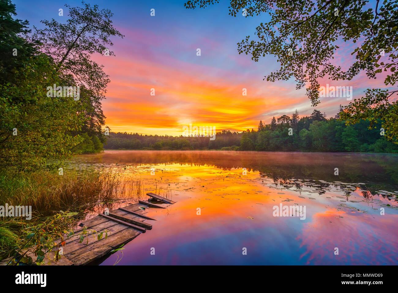 Bright sunrise on a lake - Stock Image