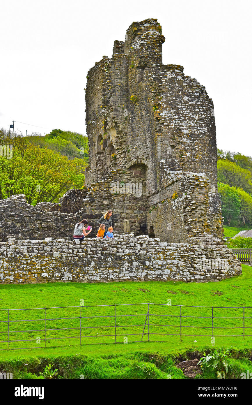 A young family group enjoy exploring the ruins of Ogmore Castle near Bridgend, South Wales. - Stock Image