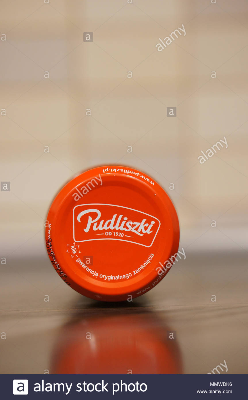 Pudliszki company logo on a tomato concentrate glass jar lying on a wooden table - Stock Image