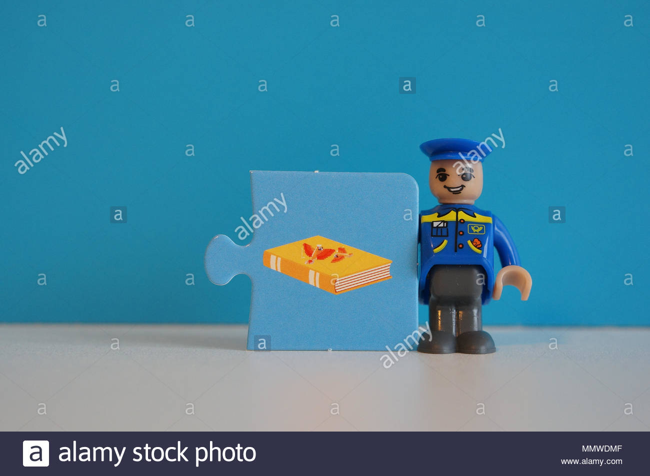 Playtive toy postman standing next to a puzzle piece with book illustration - Stock Image