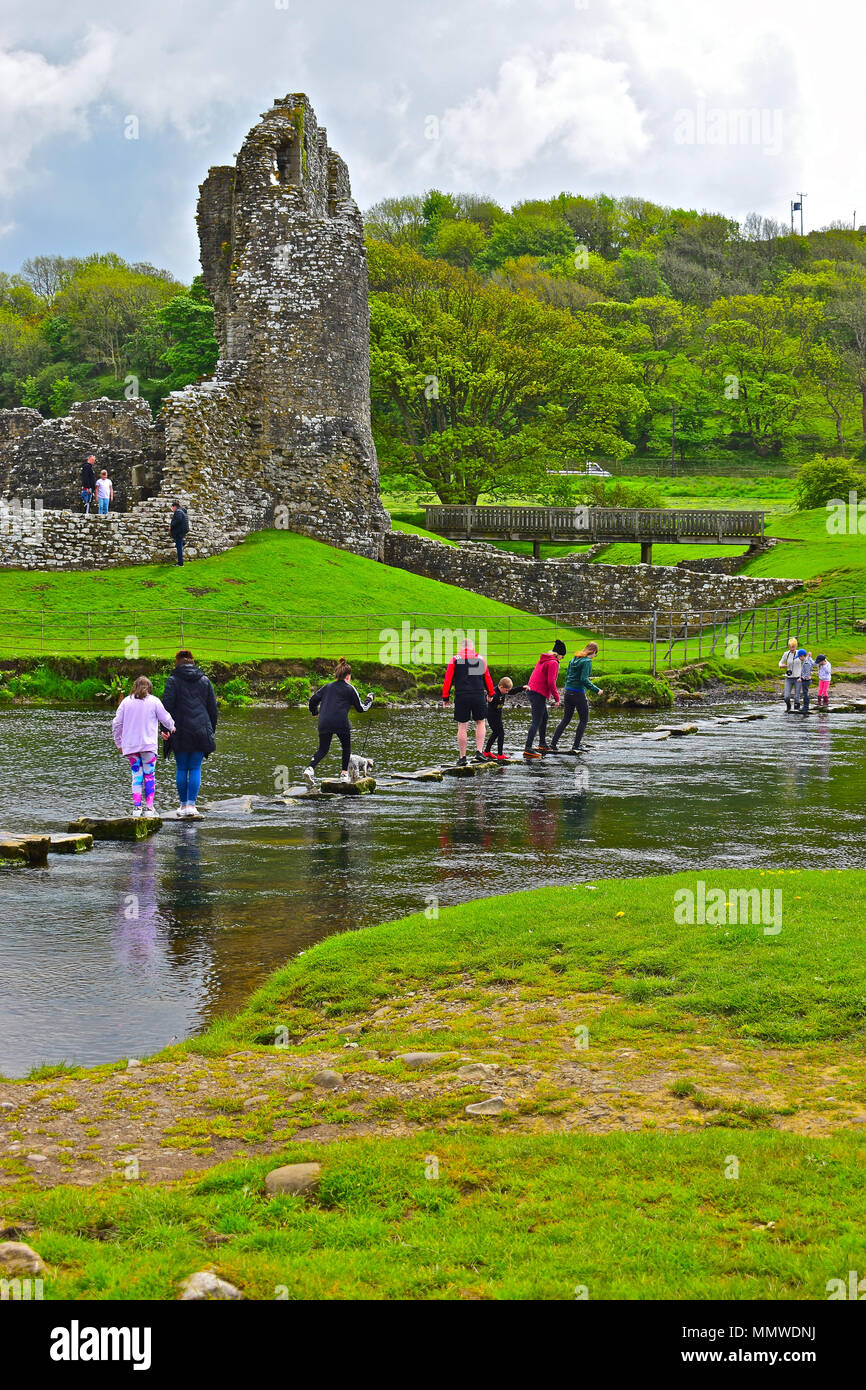 An extended family group (plus dog!) have fun crossing the stepping stones over the Ewenny River as it passes Ogmore Castle near Bridgend, South Wales - Stock Image