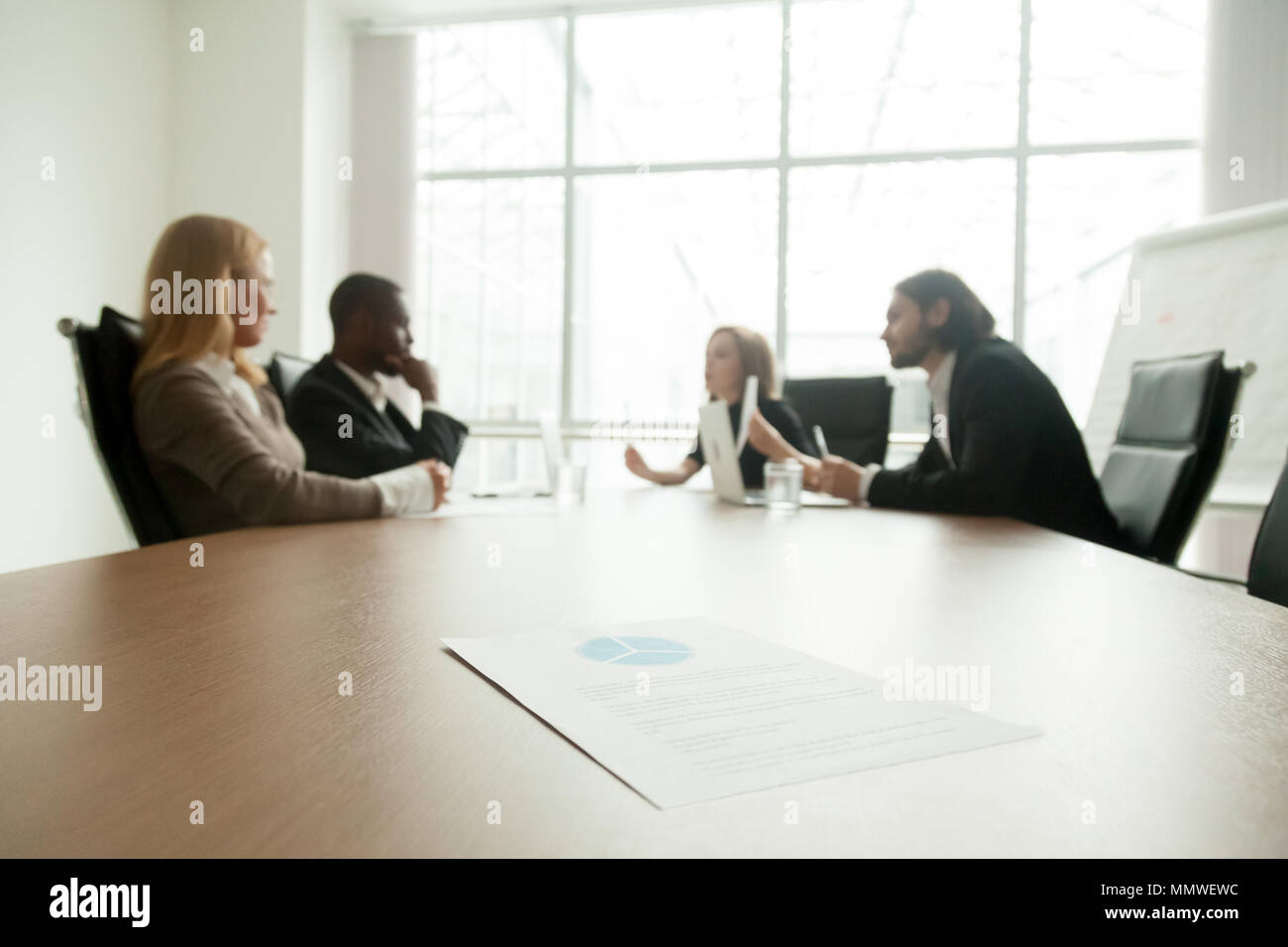 Business plan on conference table with executives meeting at bac - Stock Image