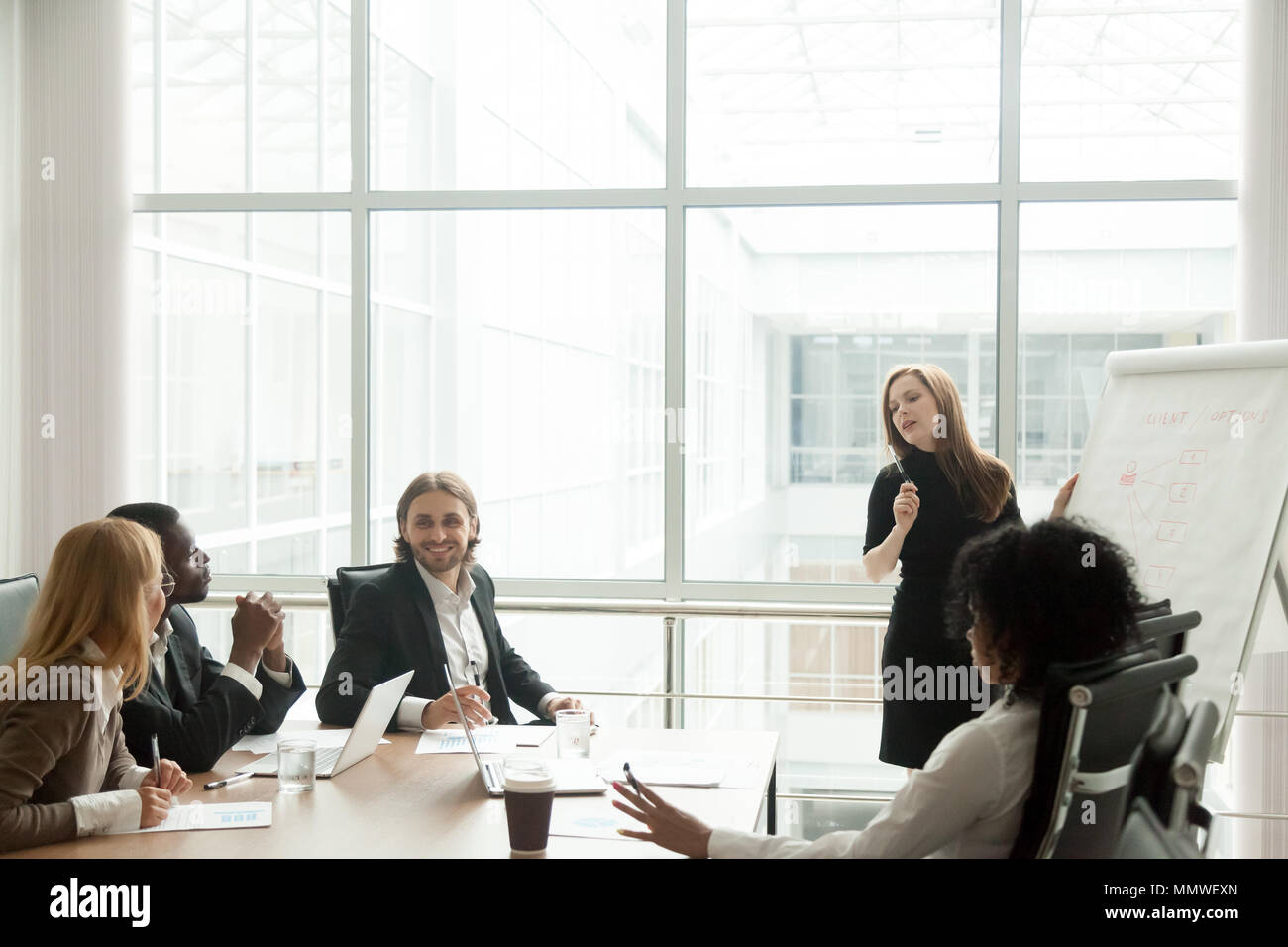 Businesswoman giving presentation for multiracial corporate team - Stock Image