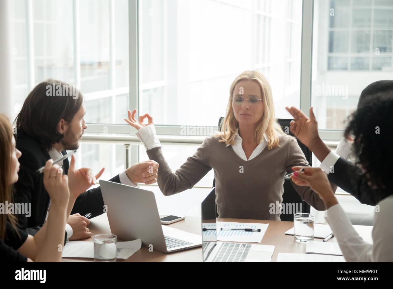 Calm businesswoman boss meditating ignoring multiracial employee - Stock Image