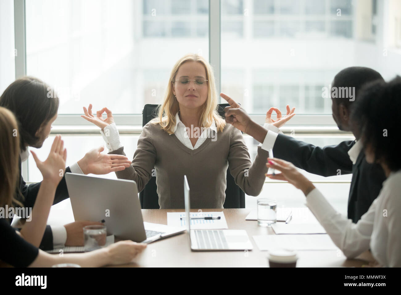 Mindful female boss calming down meditating at stressful office  - Stock Image