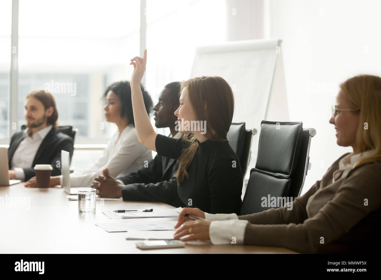 Smiling curious businesswoman raising hand at group meeting voti - Stock Image