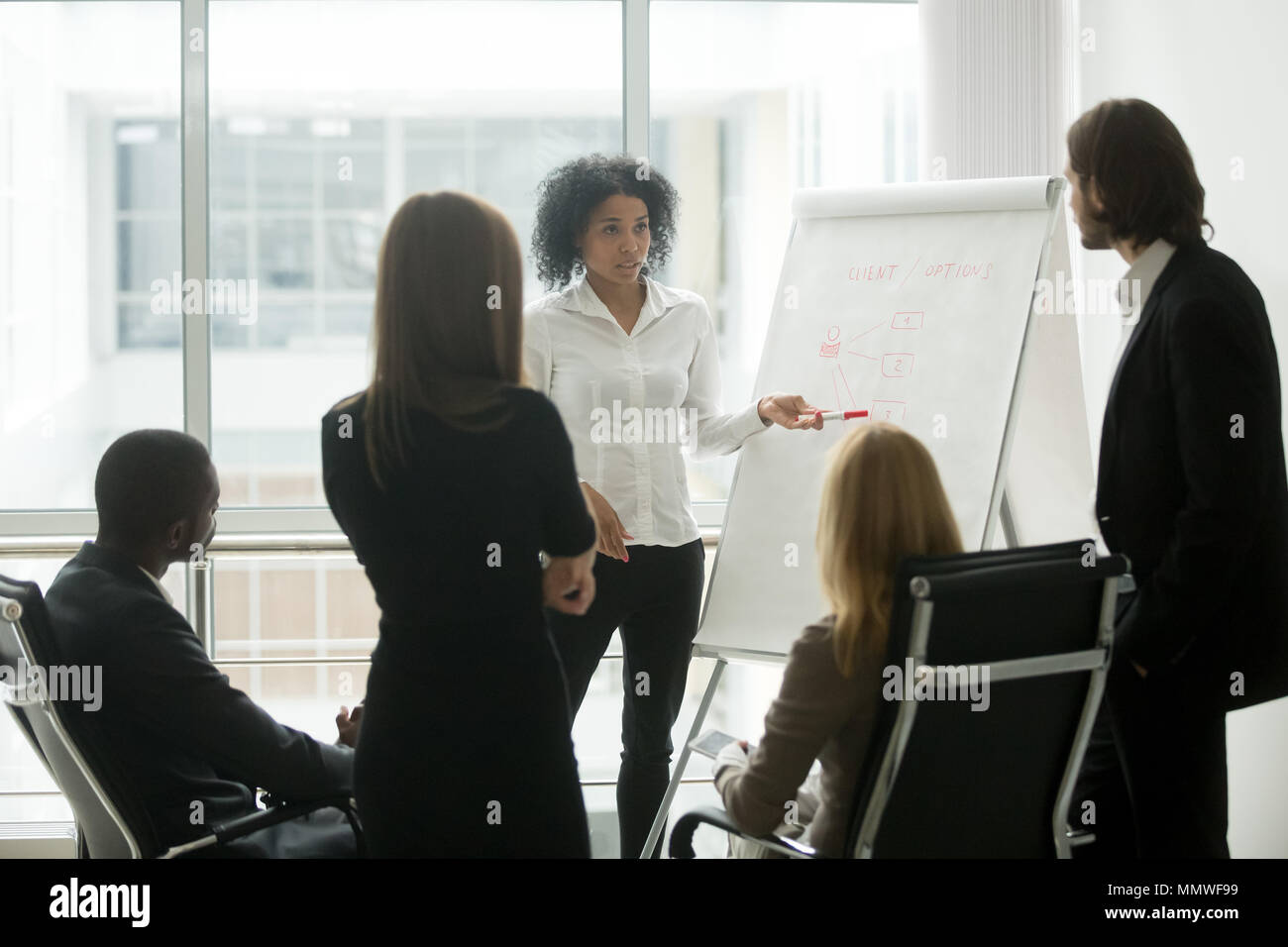 Serious african female leader gives presentation at sales team m - Stock Image
