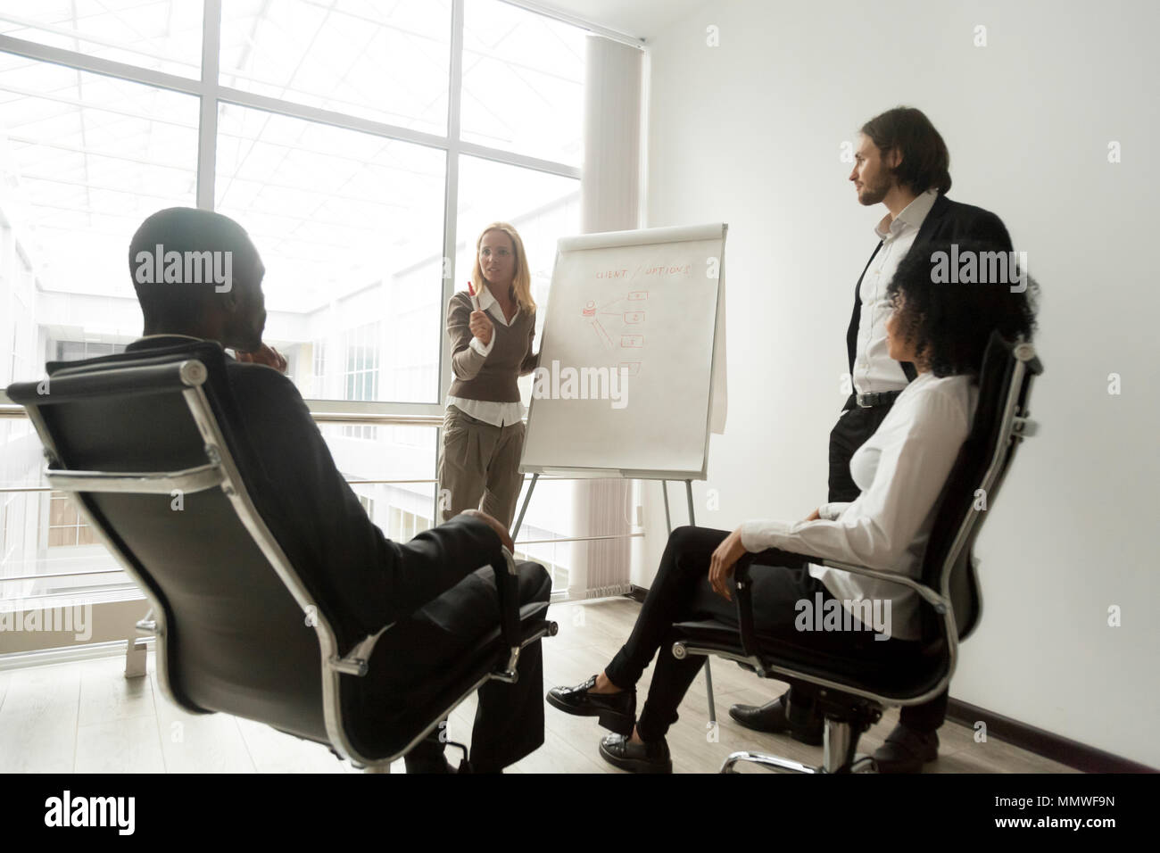 African business team listening to speakers giving presentation  - Stock Image