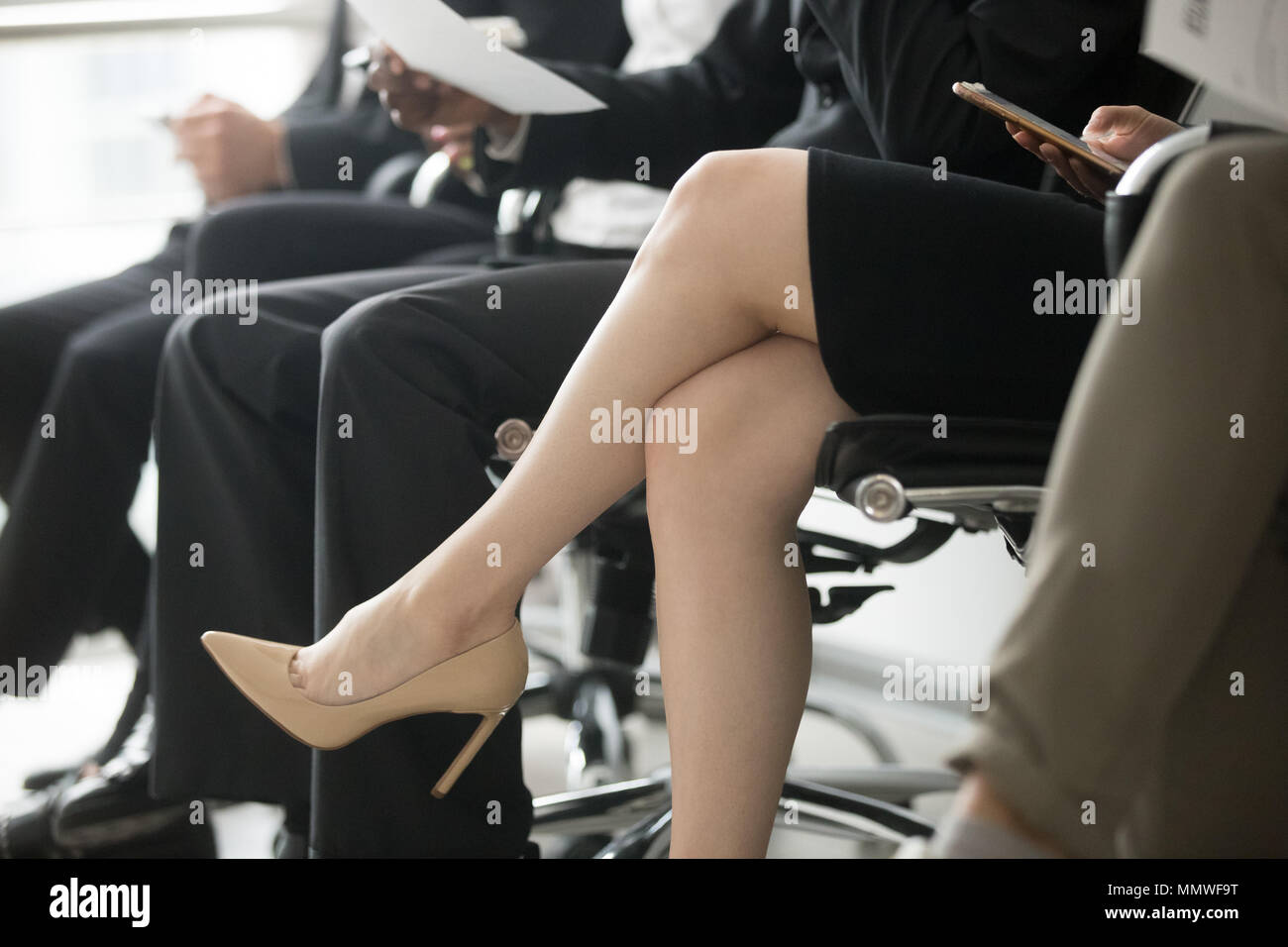 Business people sitting in row waiting for interview, legs close - Stock Image