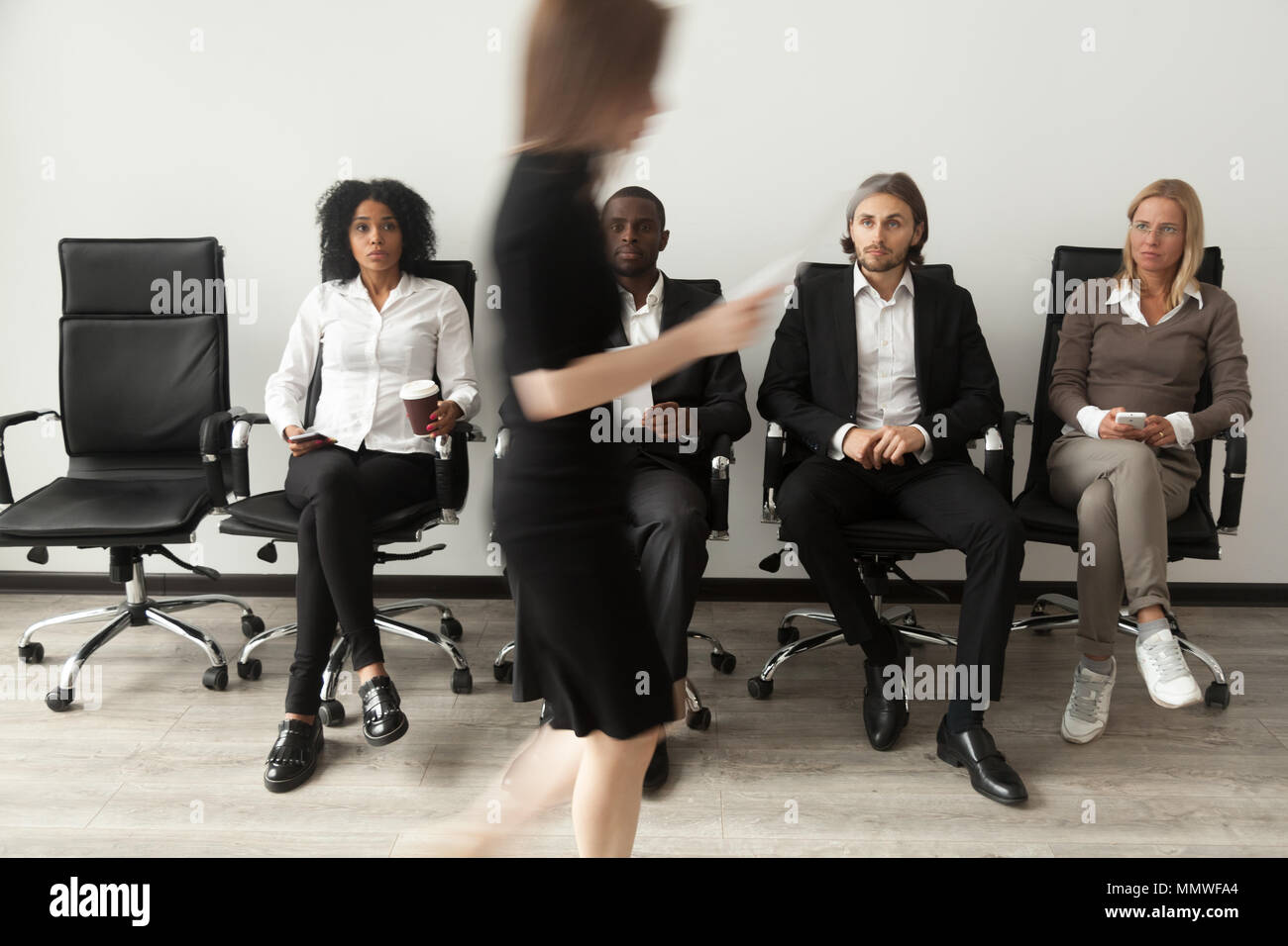 Stressed applicants sitting in queue watching rival after job in - Stock Image