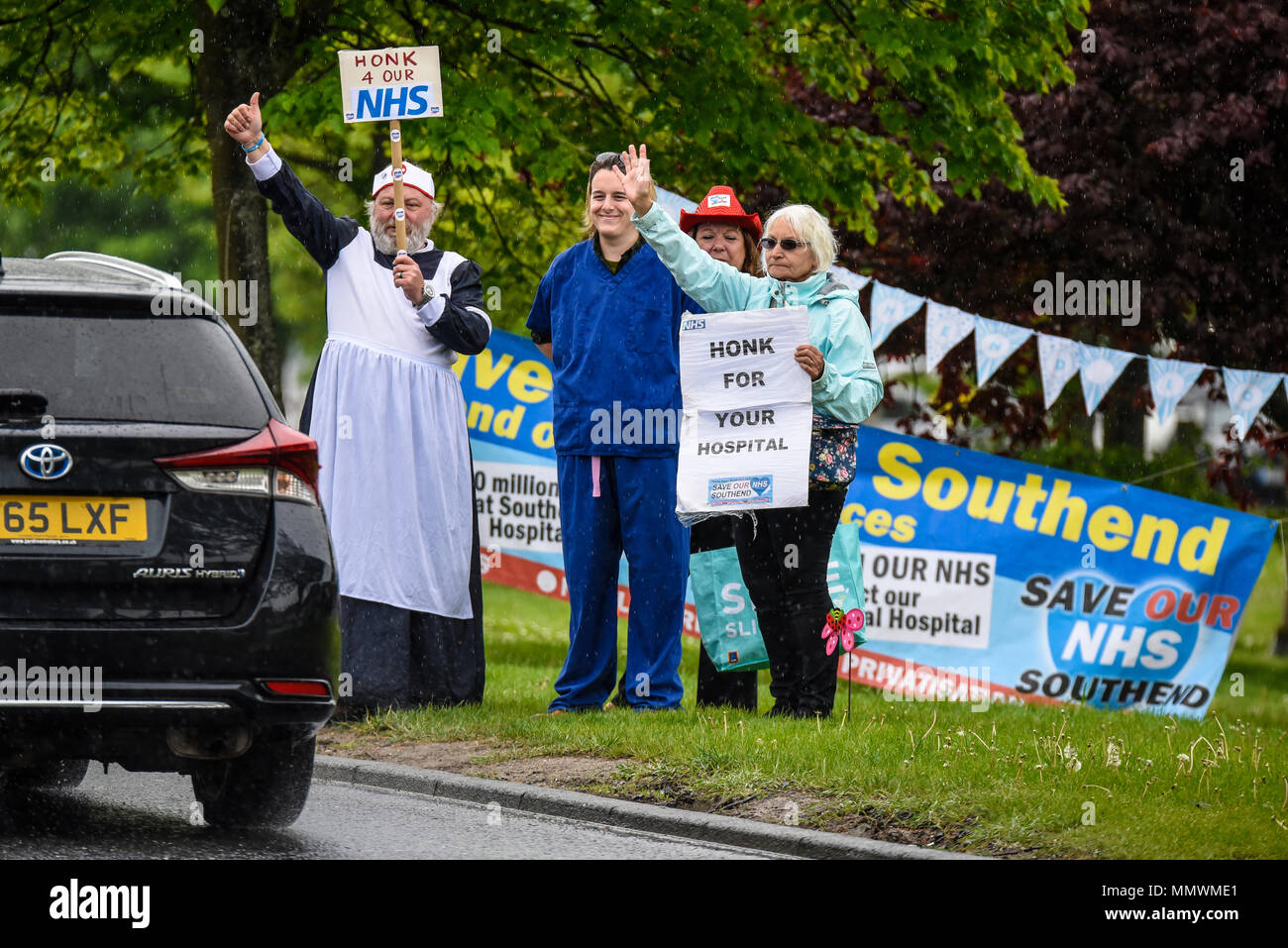 Protesters stood in the rain outside Southend Hospital to raise support against cuts. Drivers were asked to honk their car horns to show their support - Stock Image