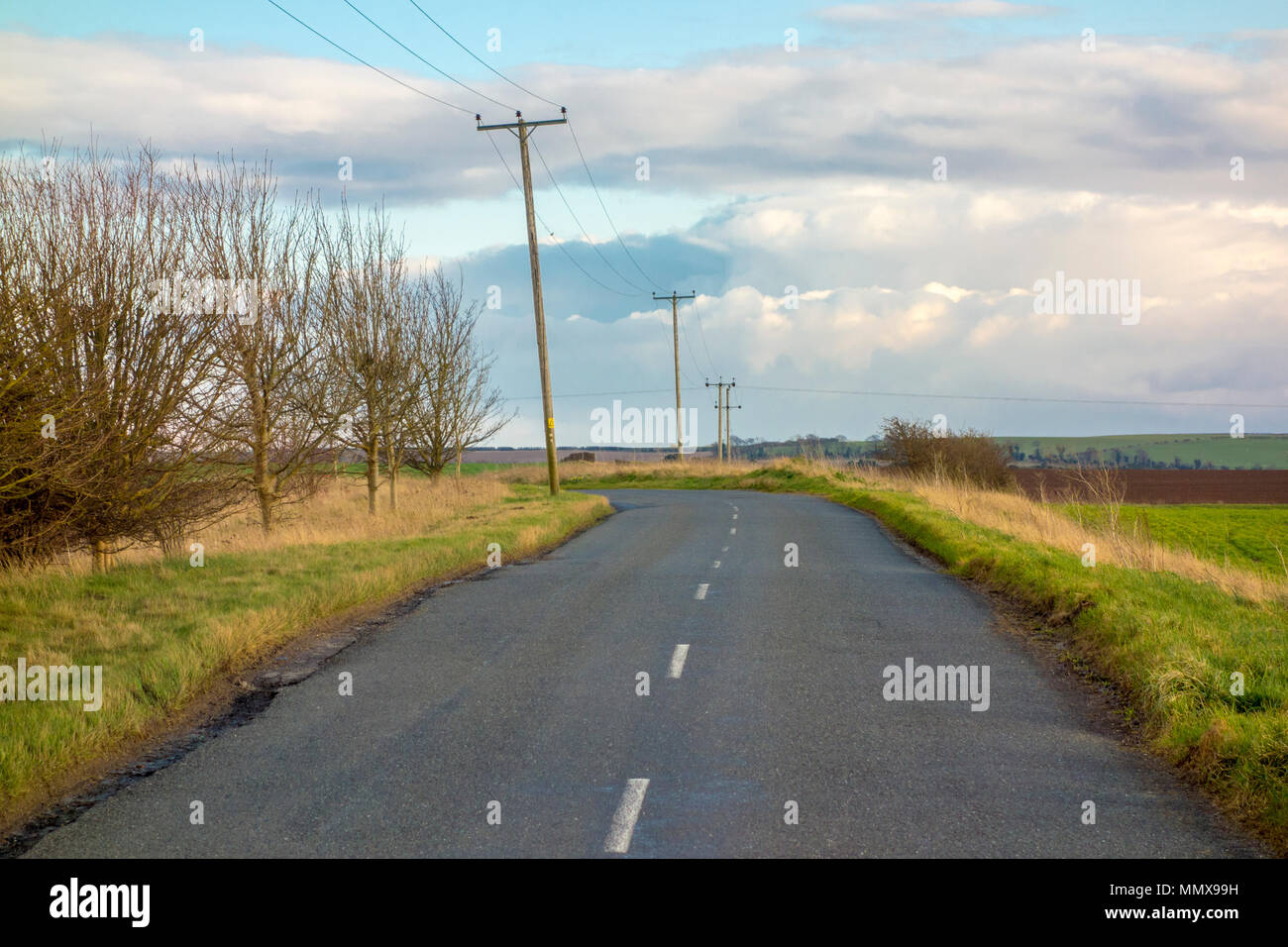 Typical empty British country lane, countryside road with telegraph poles - Stock Image