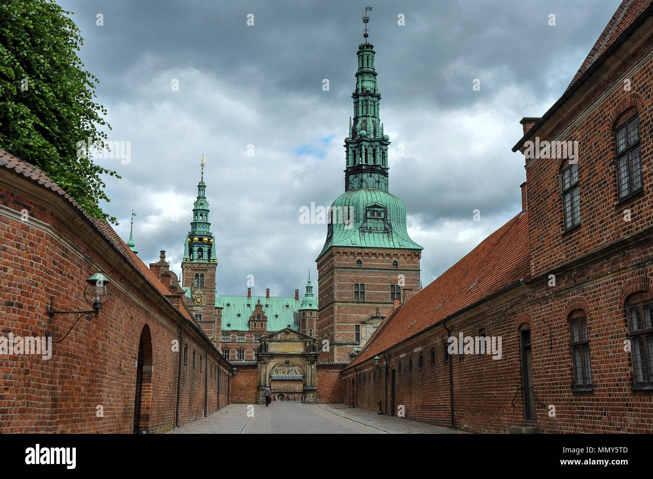 Entrance to Frederiksborg  Castle, Hillerod, Denmark.  Red brick building,  striking green towers and a stormy sky background - Stock Image