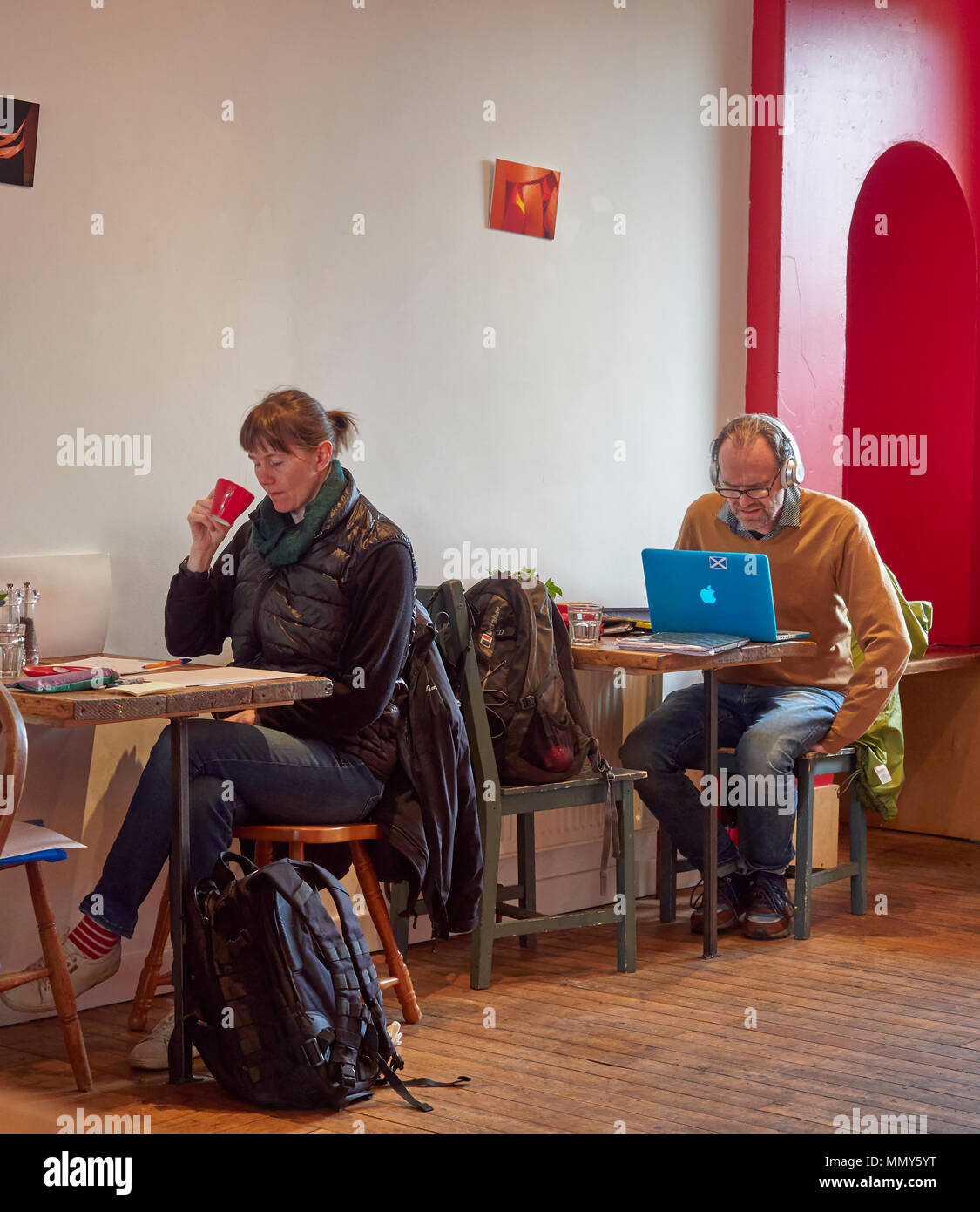 A Man and a Woman sitting at separate tables working using the free wifi of the Red Kite Cafe in Edinburgh while drinking Coffee. Scotland. - Stock Image
