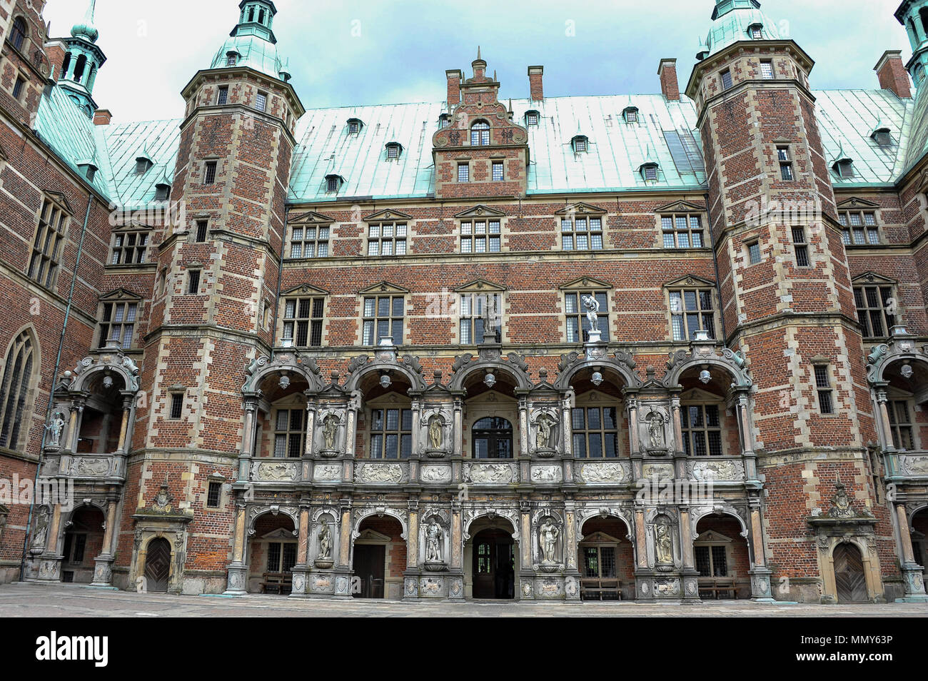 The inner courtyard, Frederiksborg  Castle, Hillerod, Denmark.  Red brick building, striking green towers and a stormy sky background - Stock Image