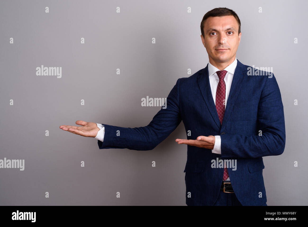 Businessman wearing suit against gray background - Stock Image
