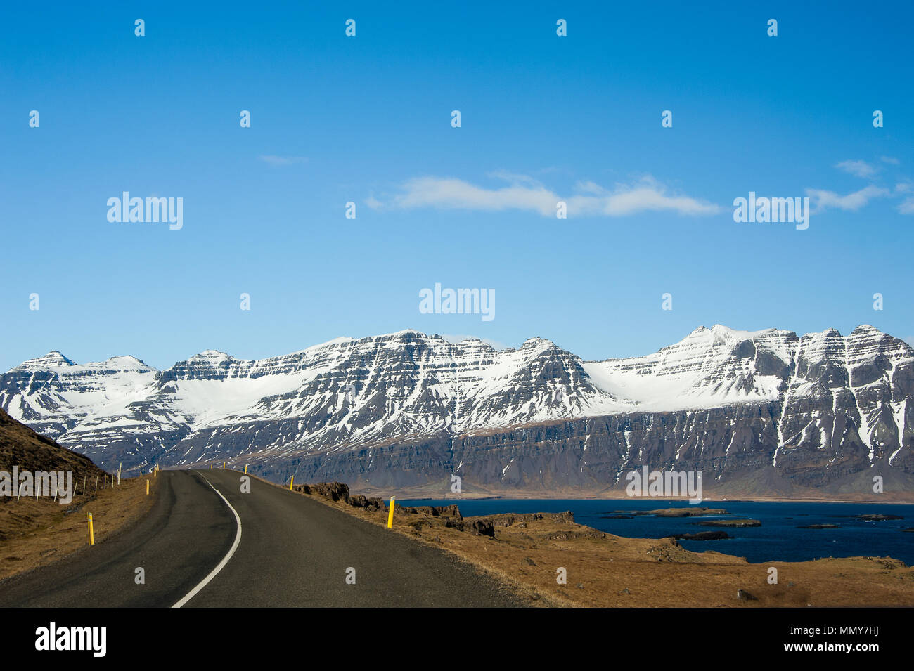 Spectacular scenery along the Eastern Fjords road near Seydisfjordur, Iceland. Stark contrast between the white, snow-capped peaks, blue water and sky Stock Photo