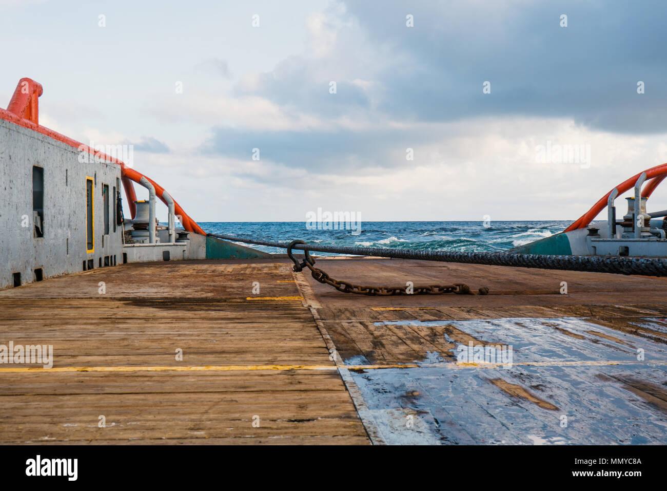 Anchor-handling Tug Supply AHTS vessel doing static tow tanker lifting. Ocean tug job. Stock Photo