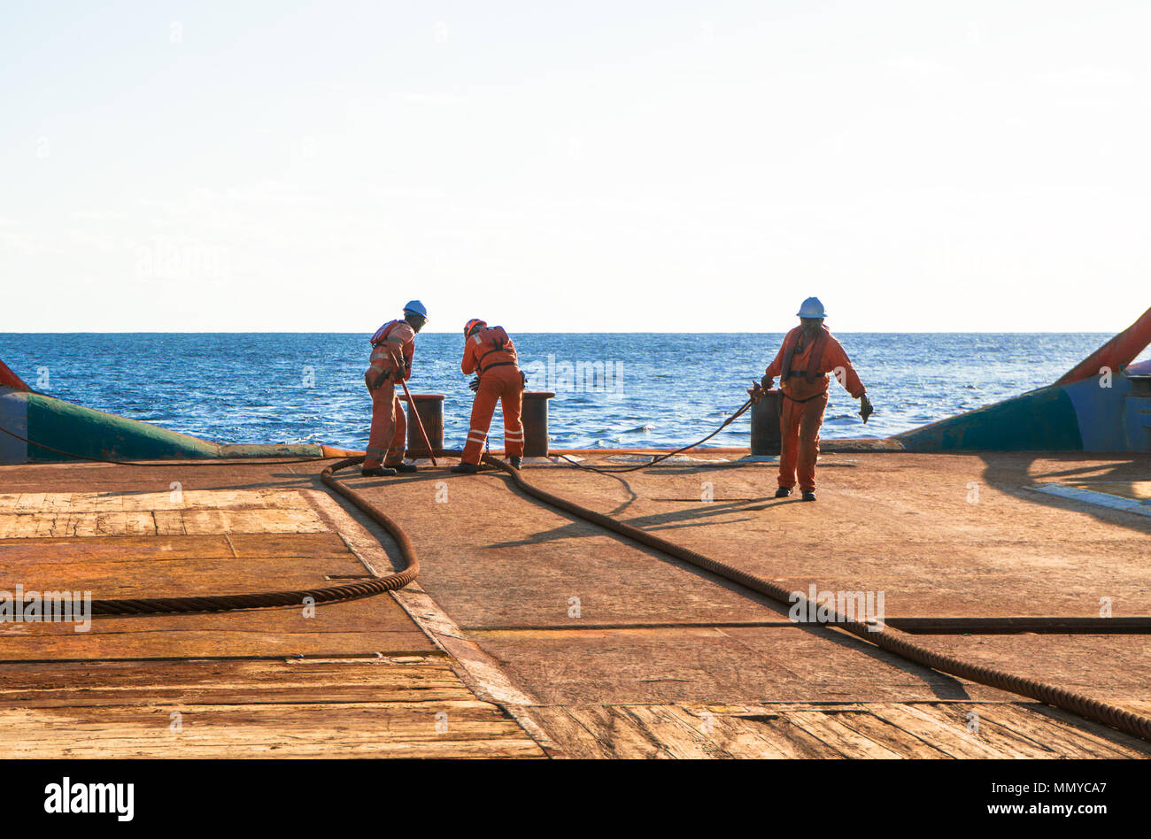 Anchor-handling Tug Supply AHTS vessel crew preparing vessel for static tow tanker lifting. Ocean tug job. 3 AB and Bosun on deck. They pull towing wi Stock Photo