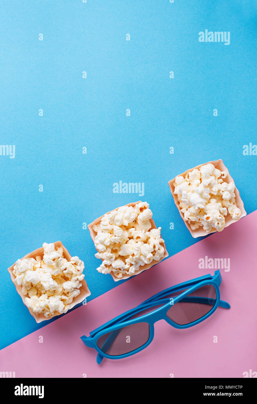 Popcorn with 3d glasses on blue background - Stock Image