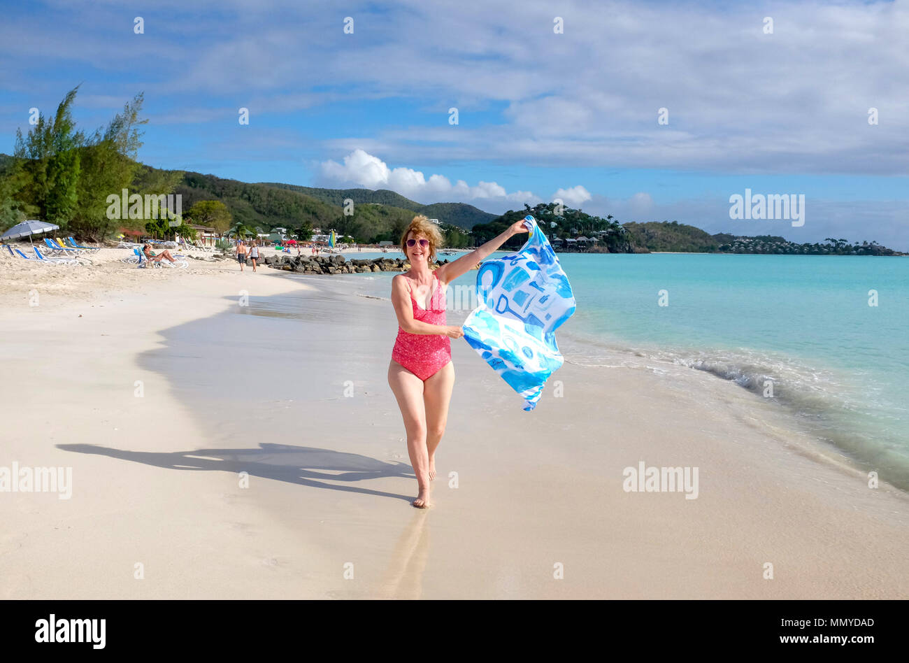 Antigua Lesser Antilles islands Caribbean West Indies - Beautiful Jolly Harbour sandy beach with woman running with a Beach Clean Designs  sarong - Stock Image