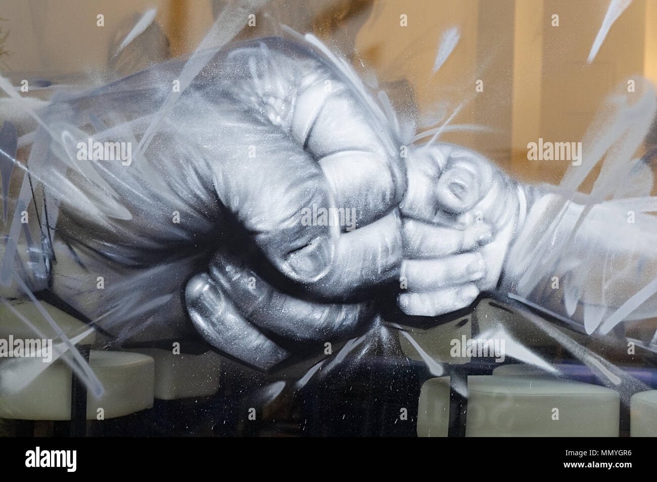 shop window display of child and adult fists clashing in love - Stock Image